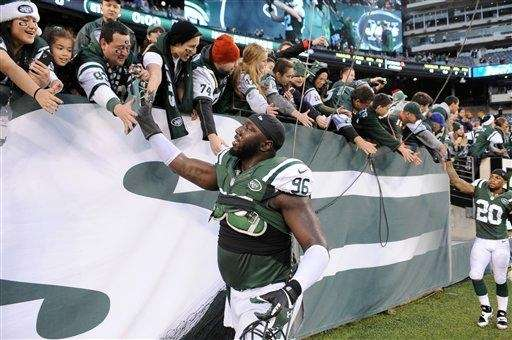 Muhammad Wilkerson reacts with fans after a game