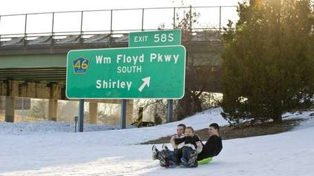 Sledders ride a hill at Sunrise Highway Exit