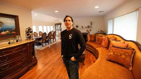 Edward Flatow stands in the living room of