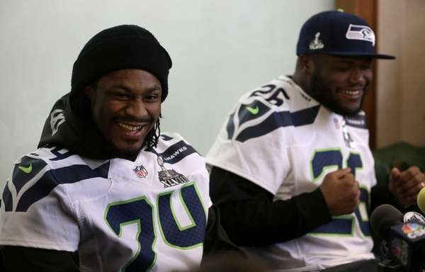 Seattle Seahawks' Marshawn Lynch, left, laughs with teammate