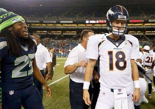 Seahawks cornerback Richard Sherman, left, talks to Broncos