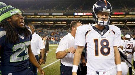 Seahawks cornerback Richard Sherman, left, talks to Broncos