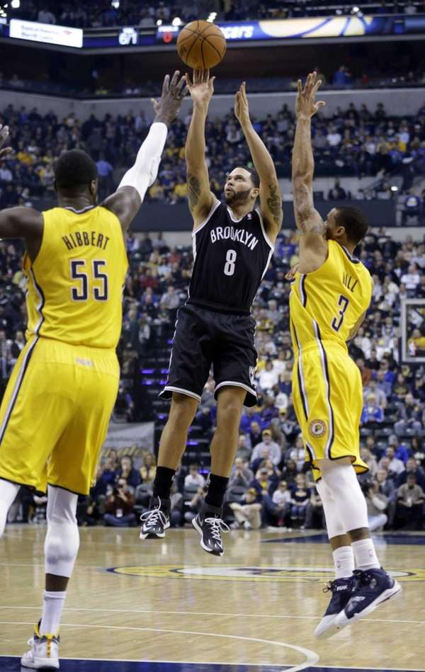 Nets guard Deron Williams shoots between Pacers center