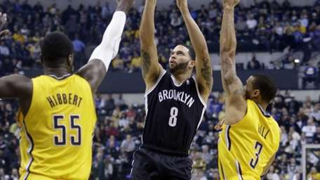 Nets guard Deron Williams shoots between Pacers center