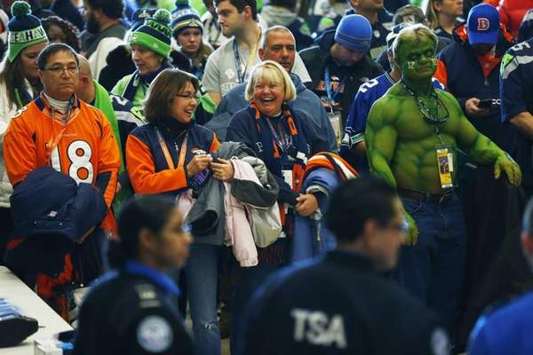 Football fans wait to go through security at