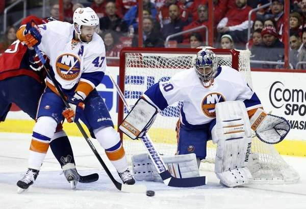 Islanders defenseman Andrew MacDonald clears the puck as