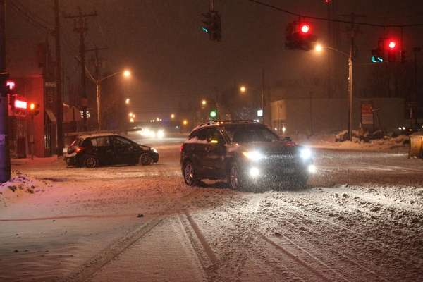 Cars navigate snow-covered Jericho Turnpike in Mineola on