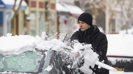 Sam Balot, of Greenport, clears snow and ice
