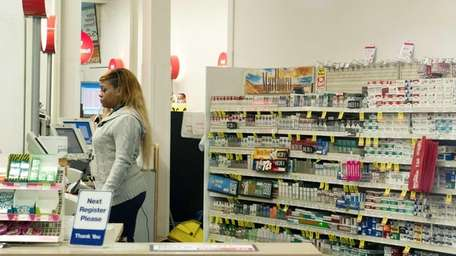 A clerk stands at the cigarette counter at
