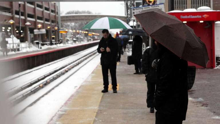 Commuters wait at the Mineola LIRR station as