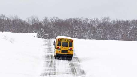 Under icy conditions, a school bus takes caution