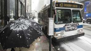 Buses navigate the snow in Midtown Manhattan on