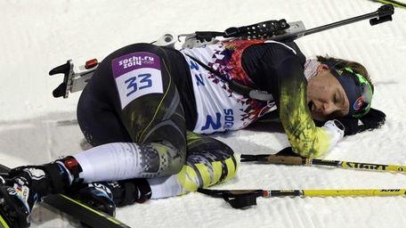Slovakia's Anastasiya Kuzmina lies in the snow after