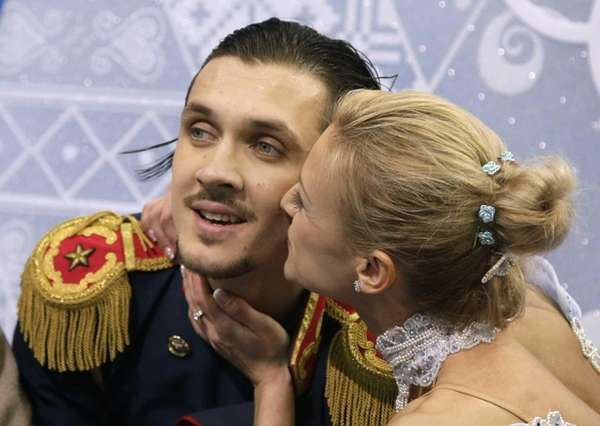 Tatiana Volosozhar kisses Maxim Trankov of Russia as