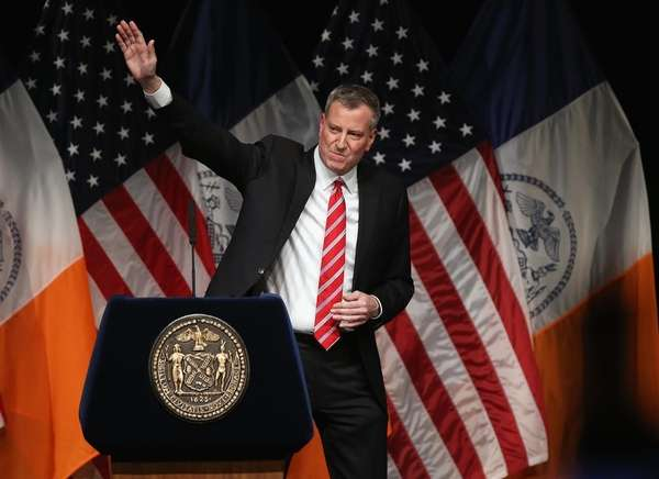 Mayor Bill de Blasio waves after delivering his