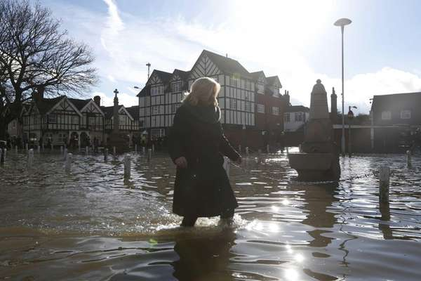 A woman wades through a flooded street, in