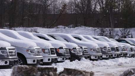 Snow-covered trucks sit in the lot at Smithtown
