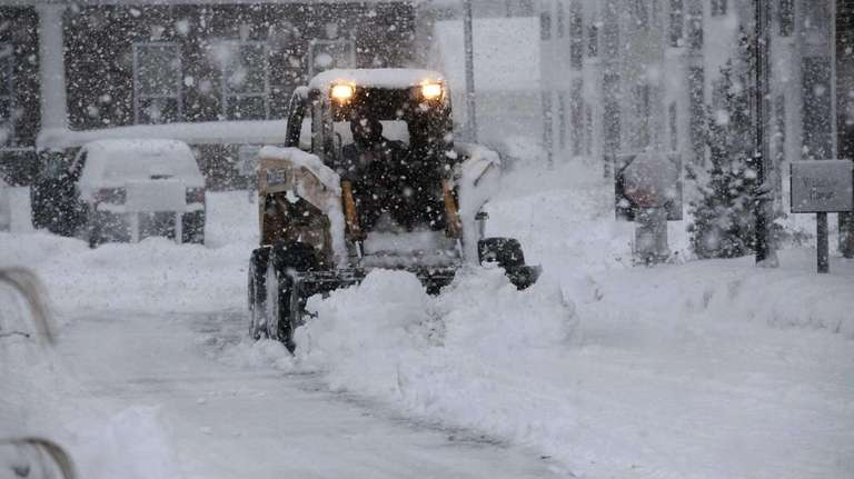 A plow works on clearing Mitchel Field Way