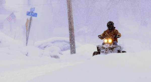 A man drives a quad in the snow
