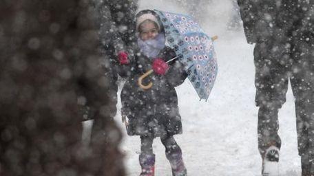 A child holds an umbrella as she walks