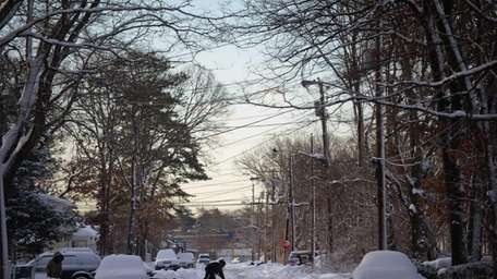 A man moves snow to the street on