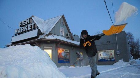 Kitt Tann cleans sidewalks Sunday morning, Feb. 16,