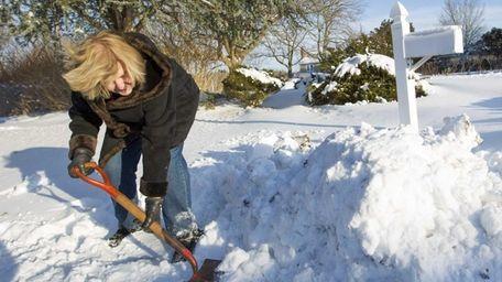 Elaine Syrkin of Cutchogue helps clear the snow