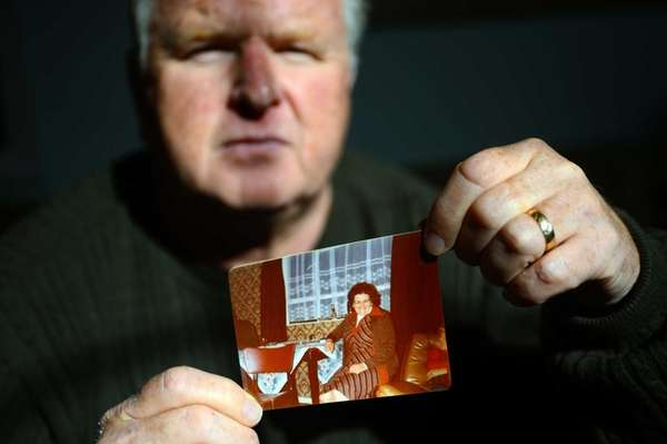 Christopher Quirin holds a photo of his mother,