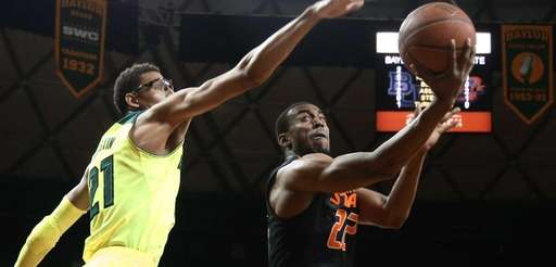 Oklahoma State guard Markel Brown, right, scores over