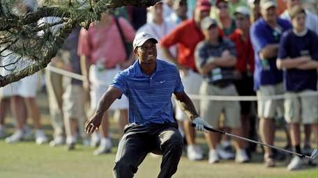 Tiger Woods nearly falls backward after hitting out