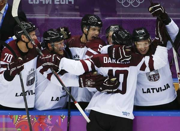 Latvia forward Lauris Darzins is congratulated by teammates