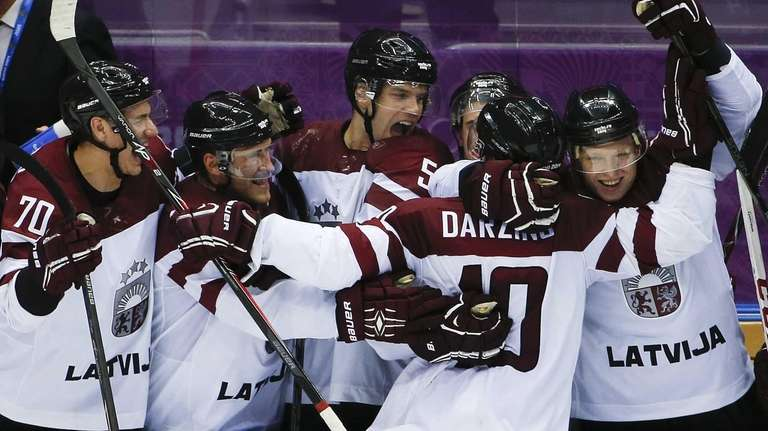 Latvia forward Lauris Darzins is congratulated by teammates