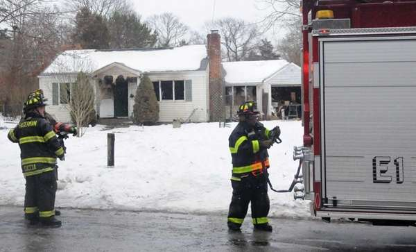 A firefighter puts away equipment after a fire