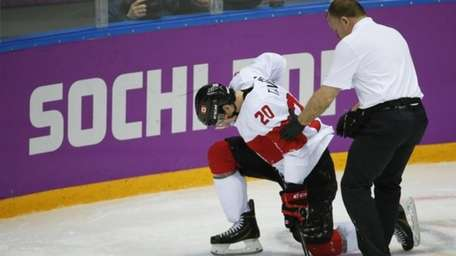 Canada forward John Tavares is helped up off