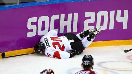John Tavares of Canada dives into the boards