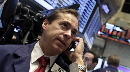 Trader Dudley Devine uses his mobile phone Wednesday,