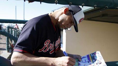 Atlanta Braves shortstop Andrelton Simmons signs an autograph