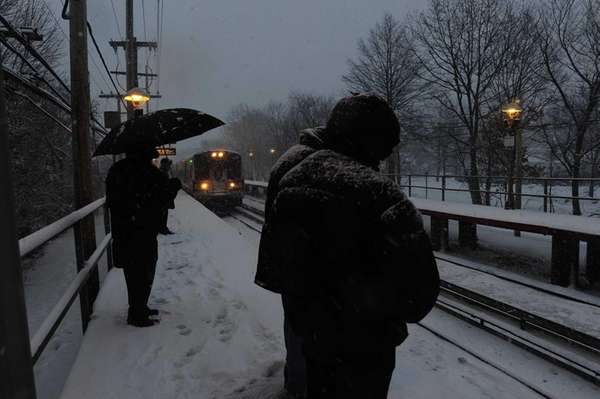 Commuters wait for their train in the snow