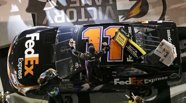 Denny Hamlin, center, cheers as he stands on
