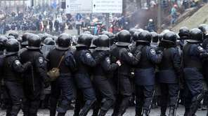 Riot police face anti-government protesters during clashes central