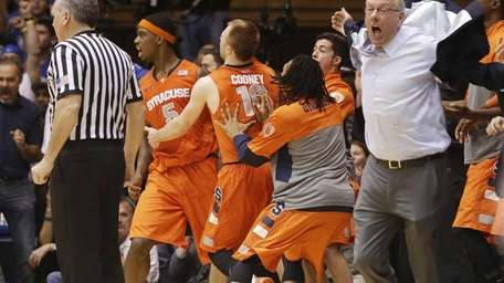 Syracuse coach Jim Boeheim, right, and players react