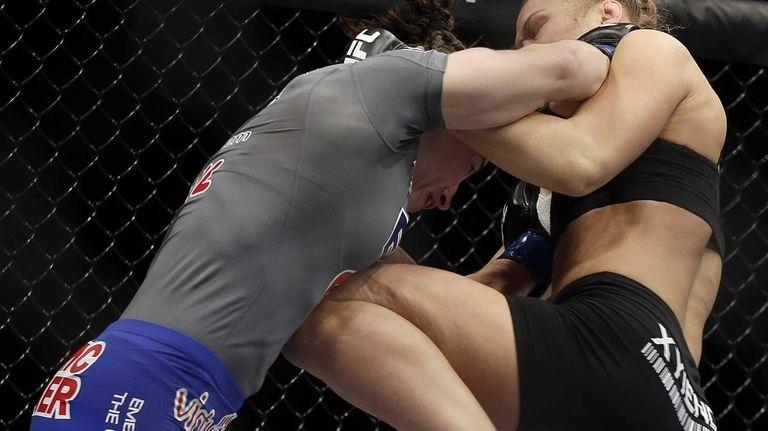 Ronda Rousey, right, knees Sara McMann during a