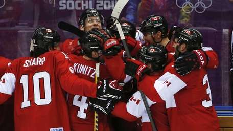 The Canadian bench celebrates their 3-0 win over