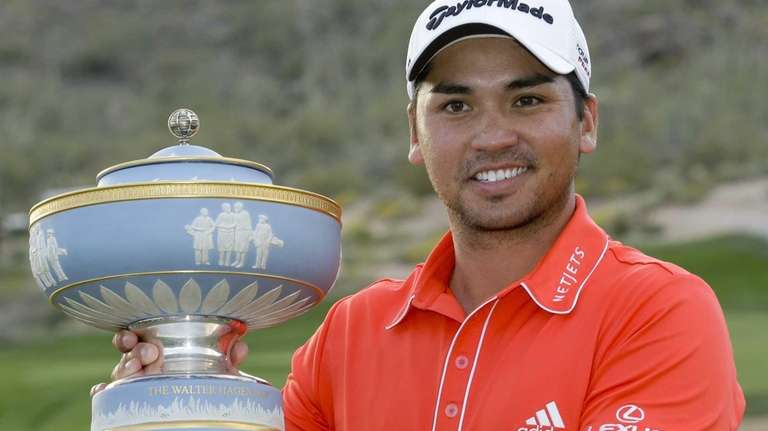 Jason Day poses with the trophy after winning
