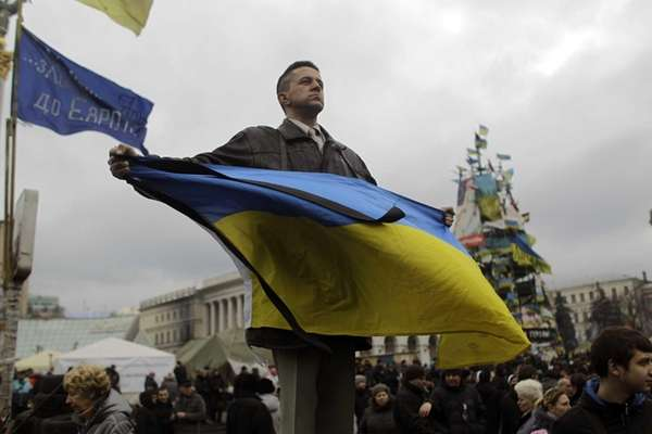 An anti-Yanukovych protester holds an Ukrainian flag in