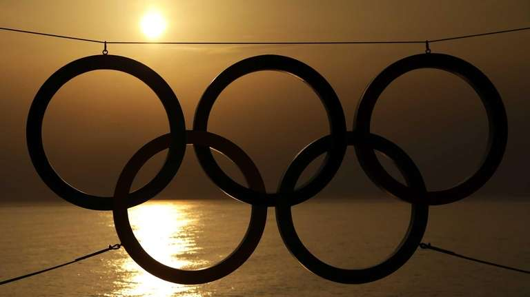 A set of Olympic Rings are silhouetted against