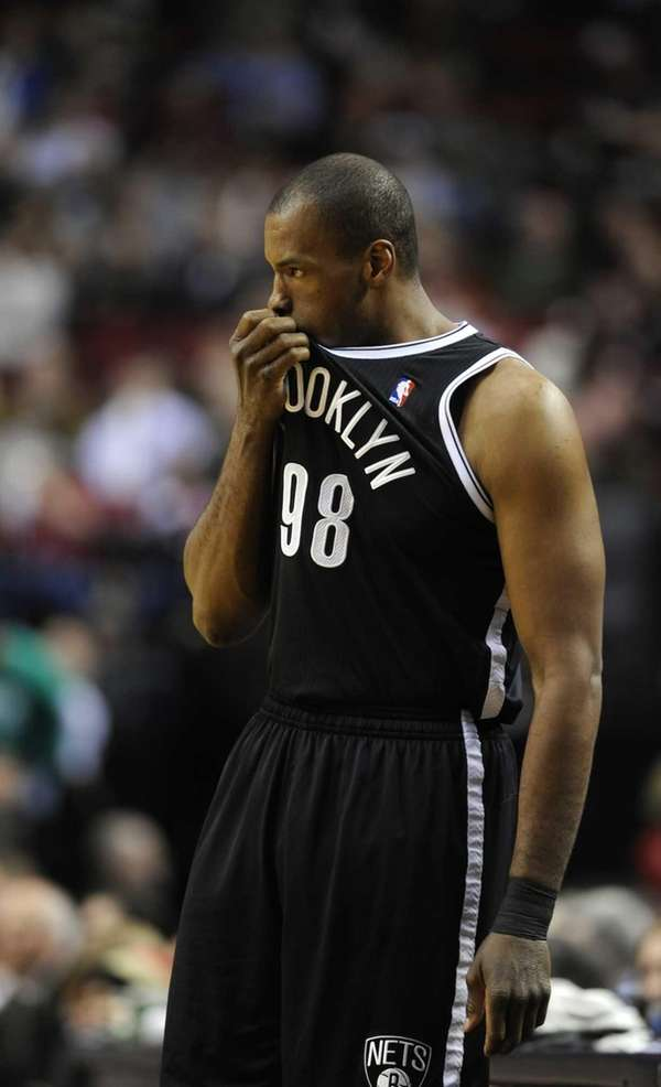 Nets' Jason Collins holds his jersey as he