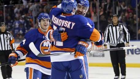 Islanders right wing Colin McDonald hugs Islanders defenseman