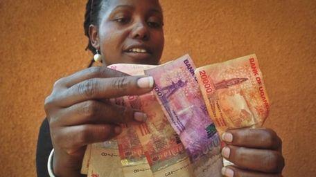 A Ugandan businesswoman who sells cereals counts Ugandan