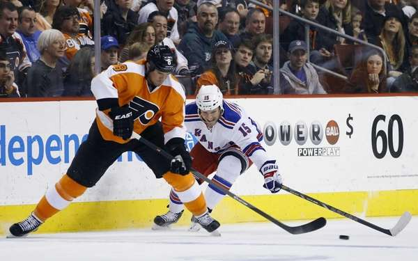 Philadelphia Flyers' Nicklas Grossmann, left, tries to keep